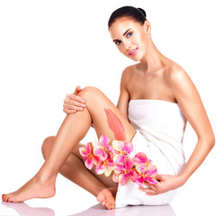 Beautiful young woman with flowers using a scrub.