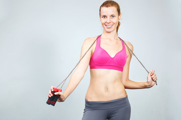 Young woman with jumping rope in her hand.