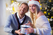 Young couple with gift at home