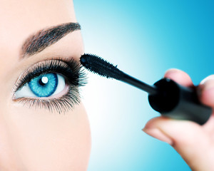 women eye with long black eyelashes and makeup brush