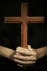 Male hands holding wooden cross