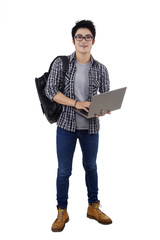 Male trendy student holding laptop