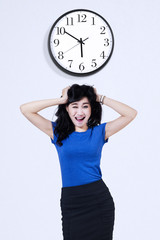 Stressed business woman with wall clock