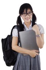 Student holding laptop in studio