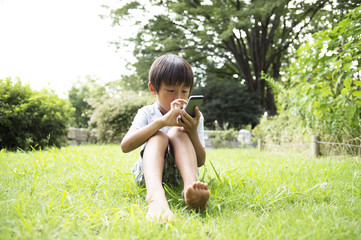 Boy to operate the mobile phone in the park