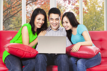 Three asian people using laptop