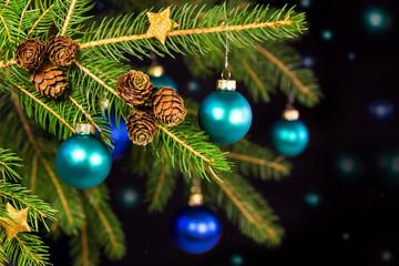 Blaue Weihnachtskugeln an Tannenbaum vor schwarzem Hintergrund