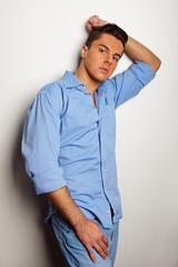 Young man at blue shirt poses at the wall
