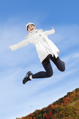 Woman leaping in autumn park