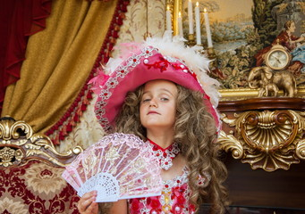 little girl in old-style dress in  beautiful ballroom
