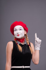 Portrait of female mime with red hat and white face grimacing wi