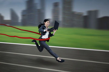 Young businesswoman running with laptop