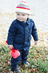 little baby boy walking away in colorful autumn park