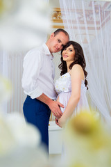 Gentle beautiful pregnant couple near tulle curtains