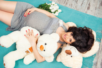 Beautiful pregnant mother with teddy bears