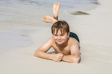 boy enjoys lying at the tropical beach