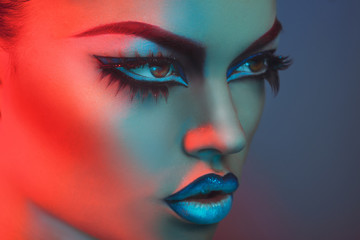 Portrait of sexy woman with healthy skin in red and blue lights