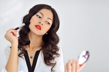 Young beautiful woman applying make-up