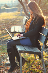 Beautiful girl works with laptop at the park