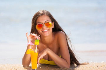 brunette woman yellow swimsuit drink cocktail