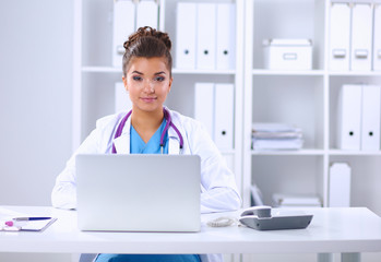 Female doctor sitting on the desk and working a laptop in hospi