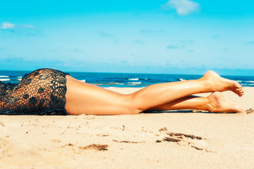 Luxuriant woman body in transparent reticulated dress on beach