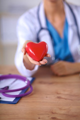 Young doctor with red heart symbol sitting at desk isolated