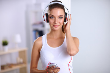 Woman with headphone listening music standing at home