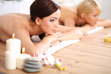 Two young beautiful women relaxing and enjoying at the spa cent