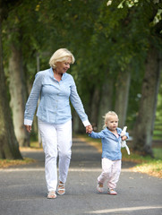 Grandmother walking with baby girl in park