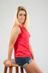 Blond woman looking thoughtful, sitting on a stool