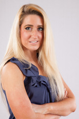 Blond woman in blue dress smiling at the camera