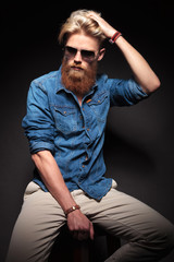 man with long red beard sitting and fixing his hair