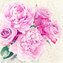 Close-up floral composition with a pink peony and roses .