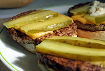 Barbecued Cheeseburgers with dill pickles on a toasted bun