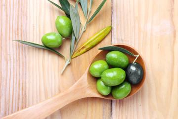 Olive verdi e una nera in un cucchiaio di legno