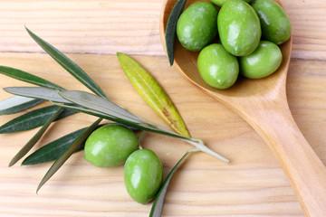 Olive verdi foglie e ramo su un tavolo in legno