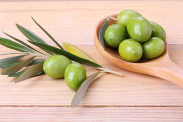 Olive verdi  in un cucchiaio in legno