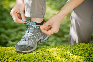 Woman Tying Walking Shoe Over Moss