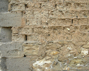 Edge of wall of mud bricks with straw and concrete bricks