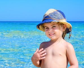 Bambina al mare con cappello azzurro