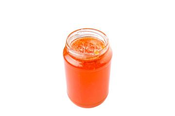 Orange fruit jam in a bottle over white background