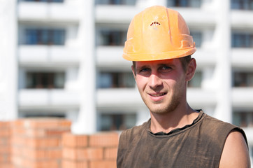 Builder worker with hard hat at construction site background