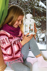 little girl dressed in a cozy sweater sits on a windowsill on Ch