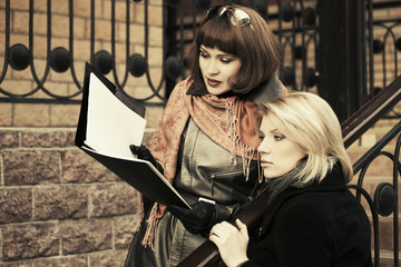 Two young fashion business women with a folder