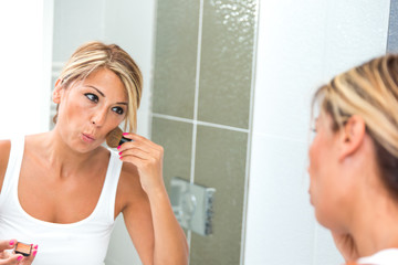 Woman putting on lipstick in front of mirror