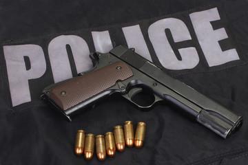 colt government m1911 handgun with ammo on police uniform