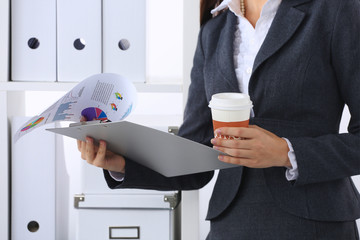 Businesswoman with folders and cup of coffee, standing in offic