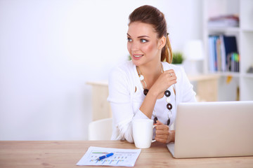 Young businesswoman sitting on the desk with cup in office