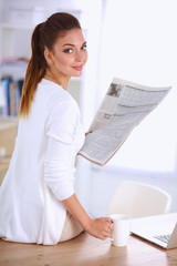 Cute businesswoman holding newspaper sitting at her desk in bri